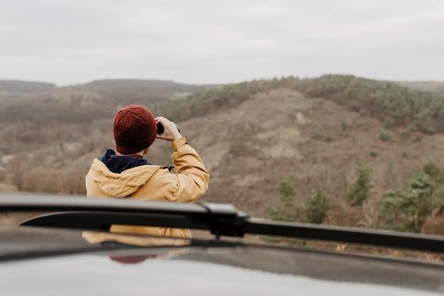 Vista trasera hombre mirando a través de binoculares Foto gratis