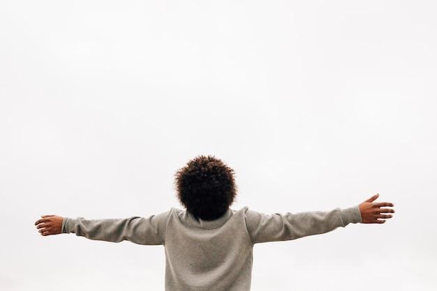 Vista trasera de un joven africano extendiendo su mano contra el fondo blanco. Foto gratis
