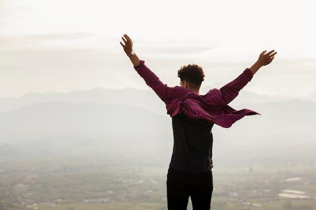 Vista trasera del joven con la mano levantada Foto gratis