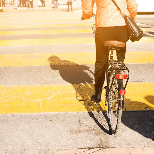 Vista trasera, de, un, mujer, andar en bicicleta, en, calle Foto gratis