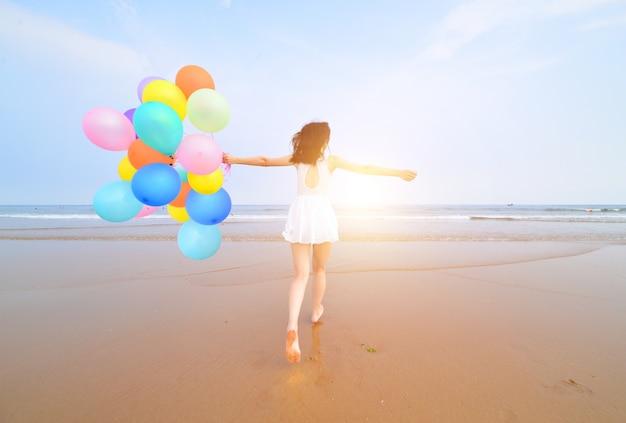 Vista trasera de mujer joven celebrando su cumpleaños en la playa Foto gratis