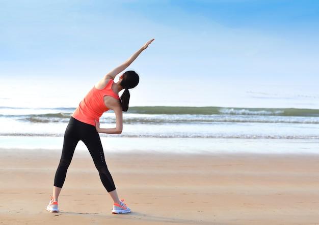 Vista trasera de mujer joven haciendo calentamientos Foto gratis