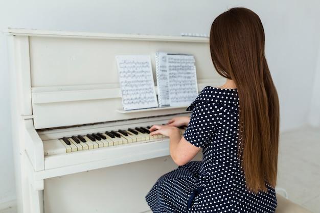 Vista trasera, de, mujer joven, con, pelo largo, tocar el piano Foto gratis