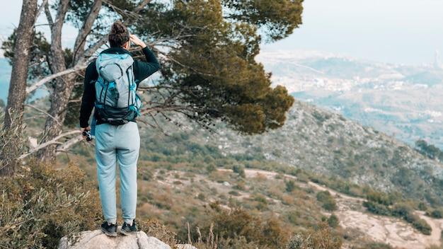 Vista trasera de una mujer con su mochila de pie sobre una roca con vistas a la montaña Foto gratis