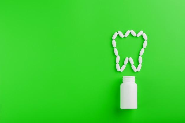 Vitamina de calcio en forma de diente derramado de un frasco blanco sobre un verde. Foto Premium