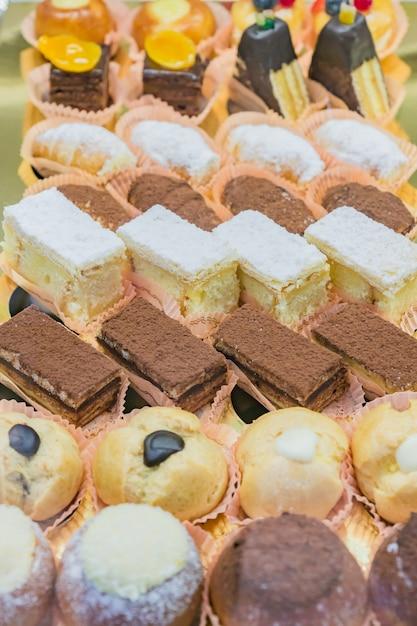 Vitrina de pastelería con variedad de mini postres y pasteles, barra de chocolate Foto Premium