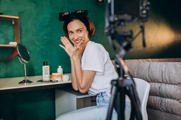 Vlogger de belleza de mujer filmando vlog sobre cremas Foto gratis