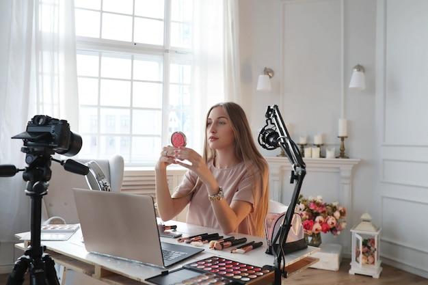 Vlogger de belleza. mujer joven grabando un tutorial de maquillaje Foto gratis