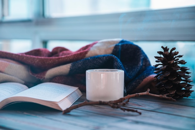 Volumen cerca de taza y plaid en mesa Foto gratis