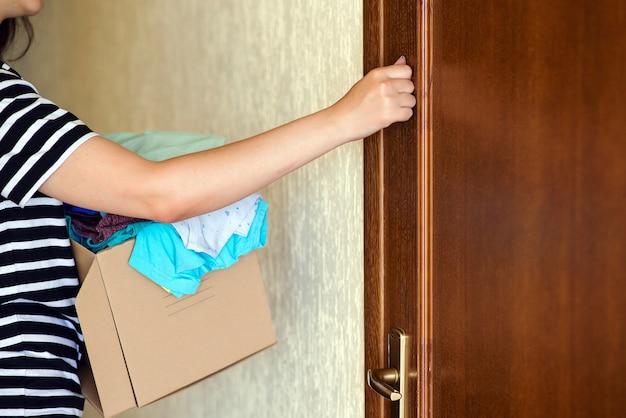 Voluntario con la caja de donaciones toca la puerta. mujer sosteniendo una caja de donación. Foto Premium