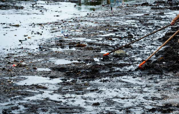 Los voluntarios usan el rastrillo para barrer la basura del mar. limpiador de playa recogiendo basura en la playa del mar. poner en orden la basura en la playa. contaminación del ambiente de playa. plástico en la orilla sucia. Foto Premium