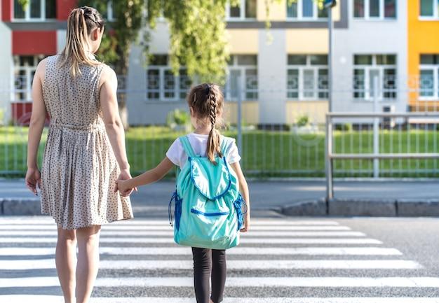 Volver al concepto de educación escolar con niñas, estudiantes de primaria, llevando mochilas para ir a clase tomados de la mano juntos caminando Foto gratis