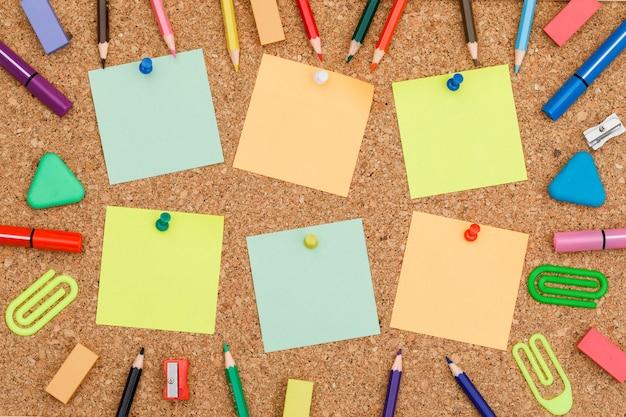 Volver al concepto de escuela con notas adhesivas fijadas, útiles escolares a bordo de fondo plano. Foto gratis