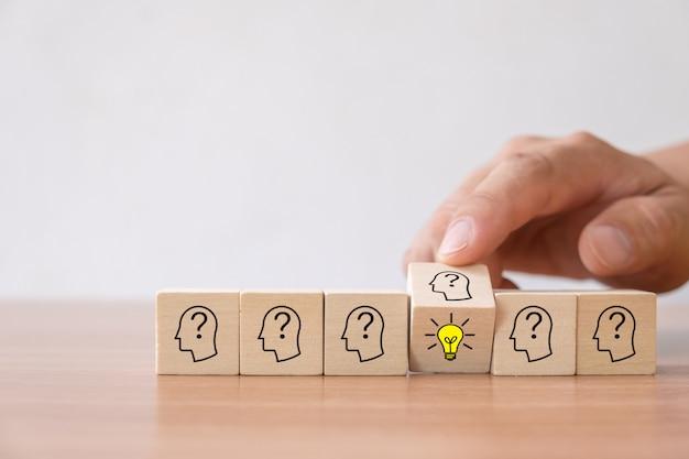 Dé la vuelta al bloque de cubo de madera con el icono de la bombilla y el símbolo humano de la cabeza no tiene idea. Foto Premium