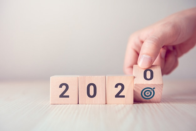 Dé la vuelta a los cubos de madera de madera con el concepto de icono de objetivo y año nuevo 2020. Foto Premium