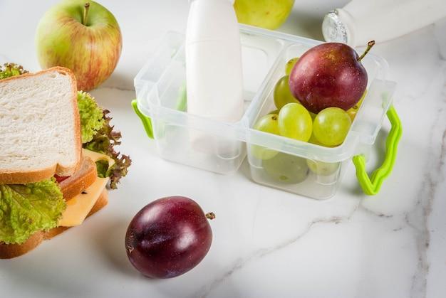 De vuelta a la escuela. un almuerzo saludable en una caja es fruta fresca, manzanas, ciruelas, uvas, una botella de yogurt y un sándwich con lechuga, tomate, queso y carne. mesa de mármol blanco. Foto Premium