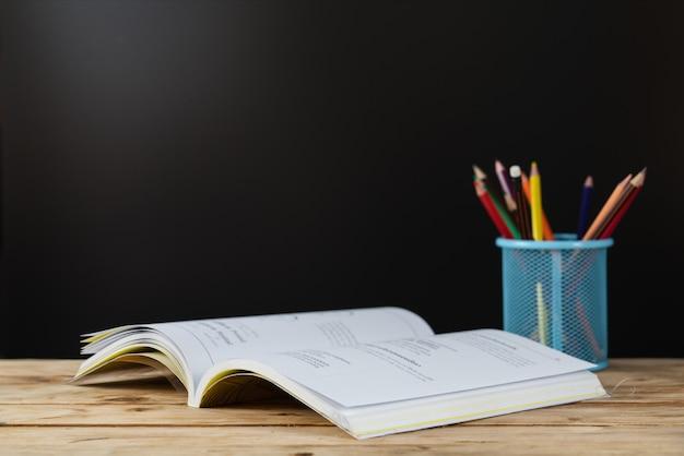 De vuelta a la escuela . libros sobre la mesa con lapiz de color en soporte Foto Premium