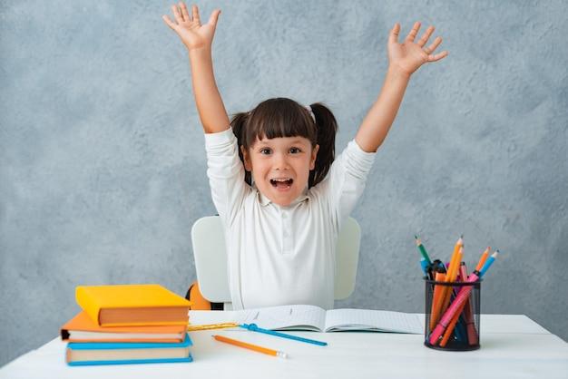 De vuelta a la escuela. linda colegiala niño sentado en un escritorio en una habitación. Foto gratis