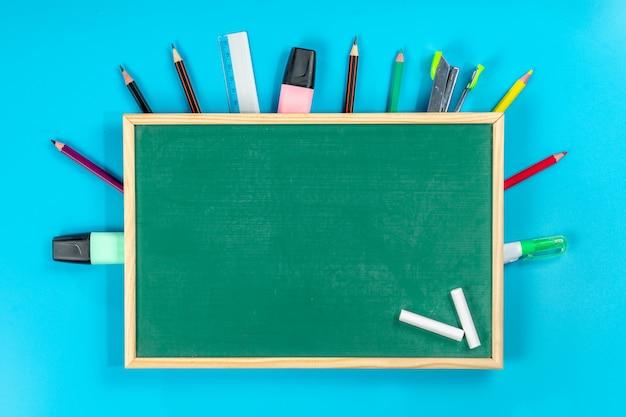 De vuelta a la escuela . útiles escolares y pizarra verde sobre azul Foto Premium