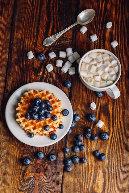 Waffles con arándanos frescos y miel en un plato, taza de café con malvavisco. Foto Premium