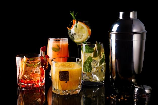 Whisky-cola cocktail, mojito-cocktail, naranja cocktail, fresa cocktail en vasos de vidrio Foto Premium