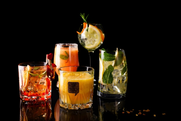 Whisky-cola cocktail, mojito-cocktail, naranja cocktail, fresa cocktail en vasos de vidrio Foto Premium