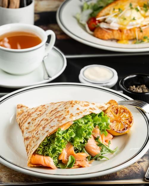 Wrap de salmón ahumado con lechuga, rúcula servida con limón a la parrilla Foto gratis