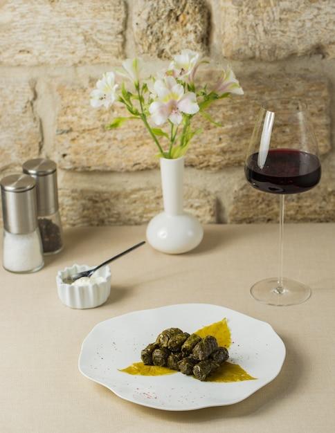 Yarpaq dolmasi, dolma de hoja de uva con una copa de vino Foto gratis