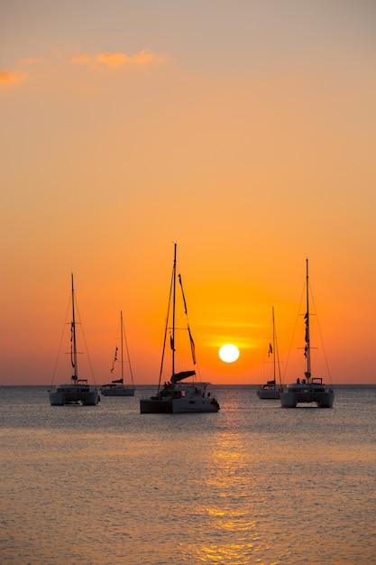 Yate en el mar durante la puesta de sol Foto gratis
