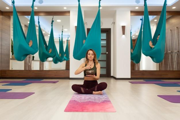Yoga entrenador con el bolo de meditación introduce a sus pupilos en trance Foto Premium