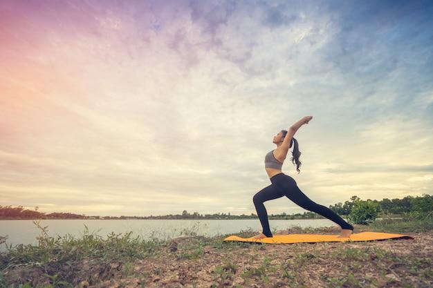 Yoga hermosa de la muchacha en el parque en el cielo hermoso del día soleado. Foto Premium