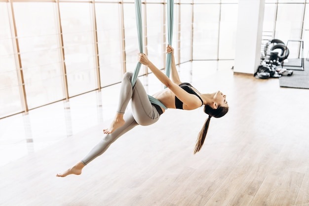 Yoga practicante de la mosca de la muchacha bastante delgada de la aptitud del cuerpo en el gimnasio. Foto Premium
