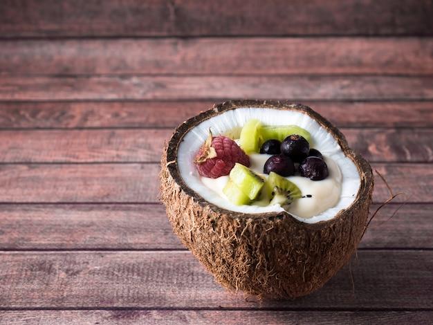 Yogur de frutas en las mitades de coco con bayas frescas sobre un fondo de madera oscuro Foto Premium
