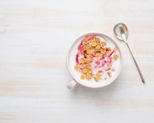 Yogur griego con mermelada y muesli en un tazón blanco Foto Premium