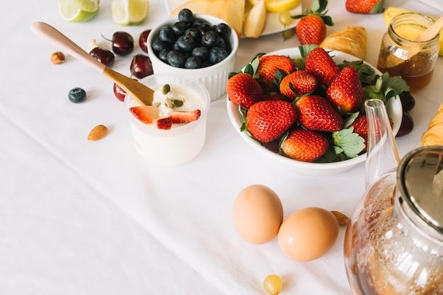 Yogur; huevo; tetera y frutas sobre fondo blanco
