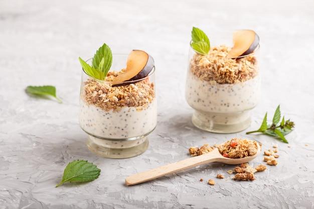 Yogur con semillas de ciruela chia y granola en un vaso y una cuchara de madera sobre fondo de hormigón gris Foto Premium
