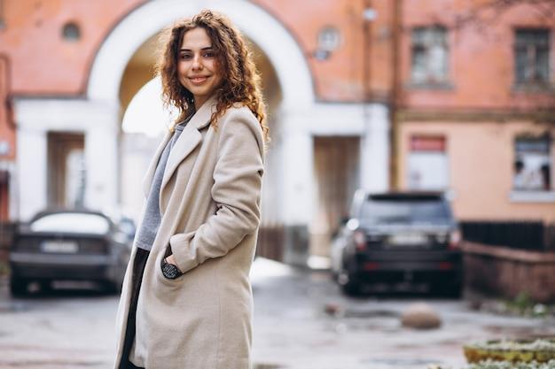 Youn mujer con cabello rizado fuera de la calle Foto gratis