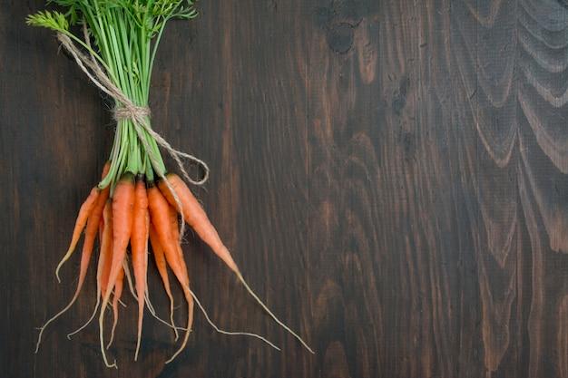 Zanahorias frescas sobre una plancha de madera vieja. zanahorias jóvenes balance de comida saludable. menú de fondo de la tabla. espacio para texto. Foto Premium