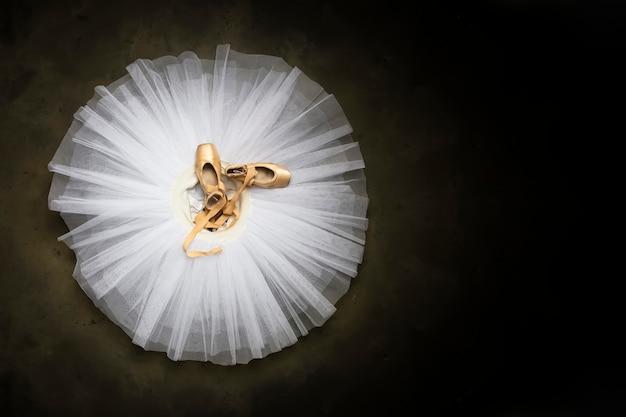 Zapatillas de ballet con cintas sobre un tutú blanco en un estudio de danza Foto Premium