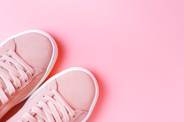 Zapatillas de deporte de color rosa femenino en un primer plano de fondo rosa, vista superior, espacio de copia Foto Premium