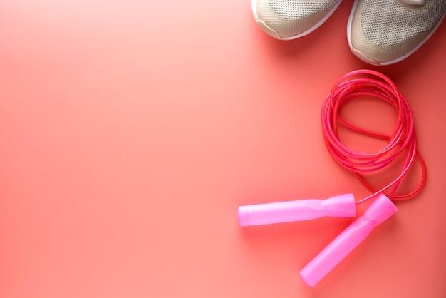 Zapatillas deportivas y cuerda de saltar sobre fondo rosa. Foto Premium