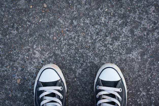 Zapatillas negras con hombre inconformista sobre hormigón. Foto Premium