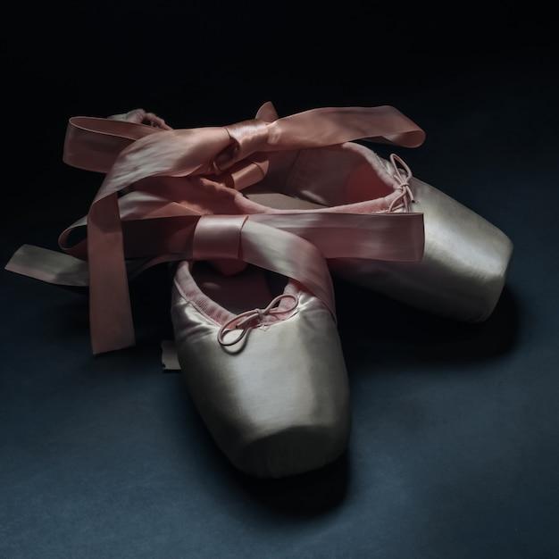 Zapatillas de punta zapatos de ballet con un lazo de cintas bellamente dobladas en la oscuridad Foto Premium