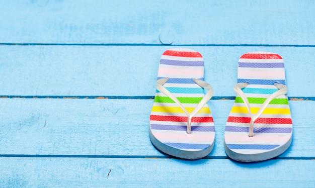 Zapato de chanclas de colores en maderas azules Foto Premium