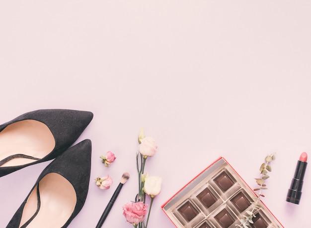 Zapatos de mujer con cosmeticos y rosas en mesa. Foto gratis