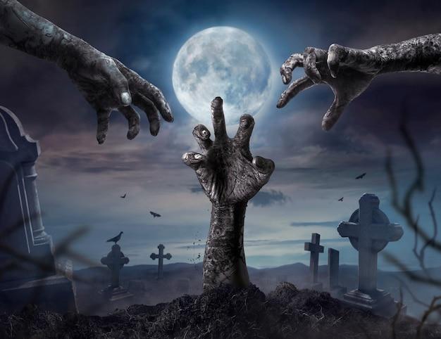 Zombie manos levantándose en la noche oscura de halloween. Foto Premium