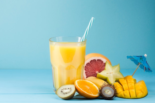 Zumo de frutas de verano sobre fondo azul Foto gratis
