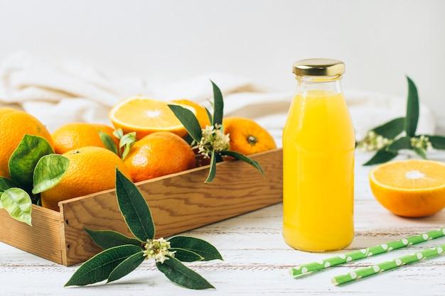 Zumo de naranja junto a pajitas y caja llena de naranjas. Foto gratis