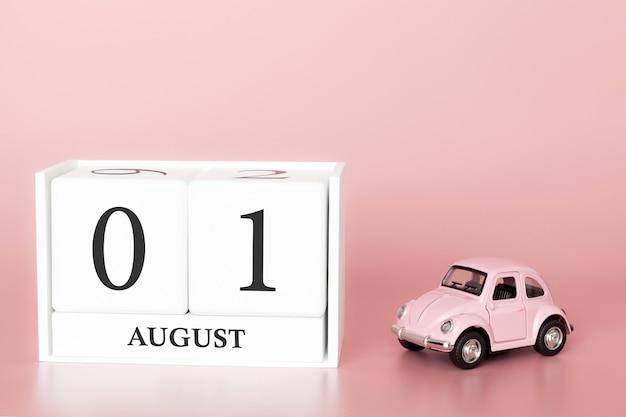 1 ° agosto, 1 ° giorno del mese, cubo calendario su sfondo rosa moderno con auto Foto Premium