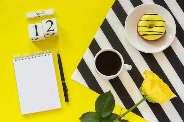 12 aprile. blocco note della ciambella della tazza di caffè su fondo giallo. luogo di lavoro elegante Foto Premium